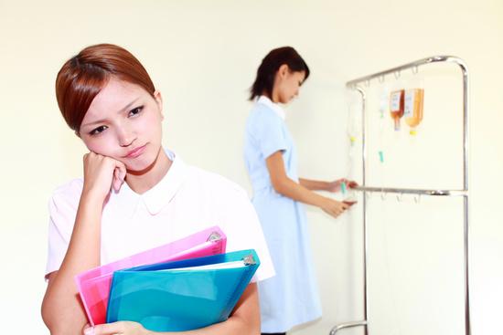 書類を持ち考える看護師